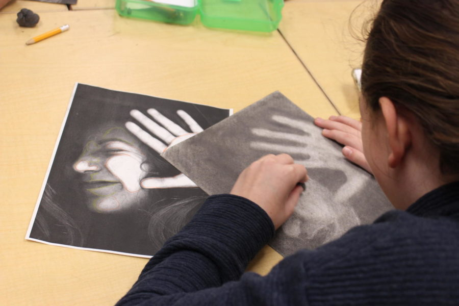 Coppell High School freshman Blanche Harris uses charcoal to add color to her black and white portrait during Honors Art I class Wednesday afternoon. Having a theme based art project, such as the charcoal used above, allows for an artist to express their talent in a creative and fun way.