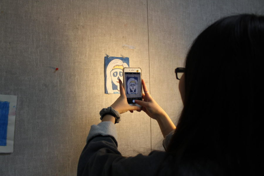 Sophomore Stacy Hong takes a picture of her day of the dead drawing for a portfolio submission on Feb. 21. Coppell High School Art I teacher, Michelle Hauske has her students working on various assignments during third period.