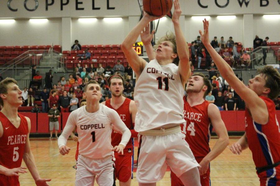 Coppell HIgh School senior Kevin Galvin jumps and scores during the third quarter of Friday nights game in the arena. The varsity boys basketball team played against JJ Pearce falling short with a final score of 56-34.