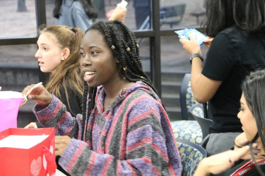 Coppell High School senior Rachel Okereke talks with friends at the Red Jacket Valentines Day party in the library during third period today. For the first time, the Red Jackets social committee planned a celebratory party for the hardworking seniors.