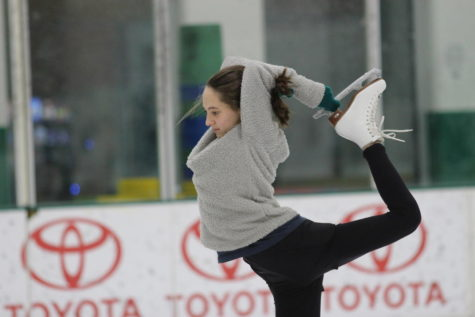 Coppell High School sophomore figure skater Kate Strong grabs a hold of the blade of her skate as she practices the biellmann pose during figure skating practice on Feb. 2 at the Dr. Pepper Star Center in Farmers Branch. Strong has been figure skating since she was eight years old and is also a CHS Lariette.