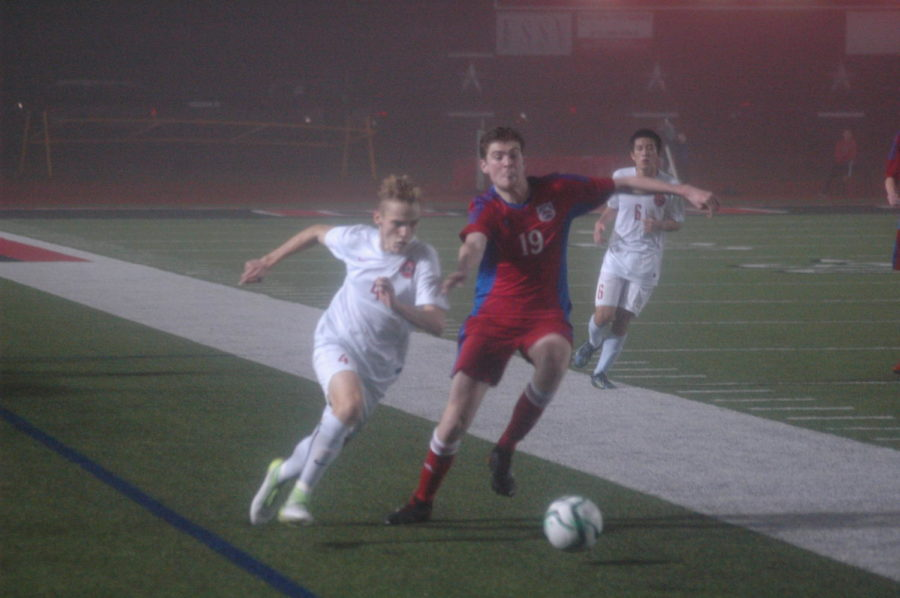 Coppell senior Josh Strong chases down a loose ball against a J.J. Pearce player on Tuesday night at Buddy Echols Field. The Cowboys lost to the Mustangs, 1-0, on Tuesday night.