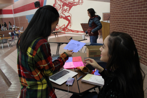 Coppell High School senior Student Council officer Ashley Benyahoun sells carnation grams to senior Sol Hong on Thursday during lunch in the commons. The CHS Student Council is holding a Valentine's Day Carnations fundraiser where students buy and request carnations to be sent to their friends or teachers. Carnations costs $1 each and are sold during all lunches in the cafeteria through Friday.