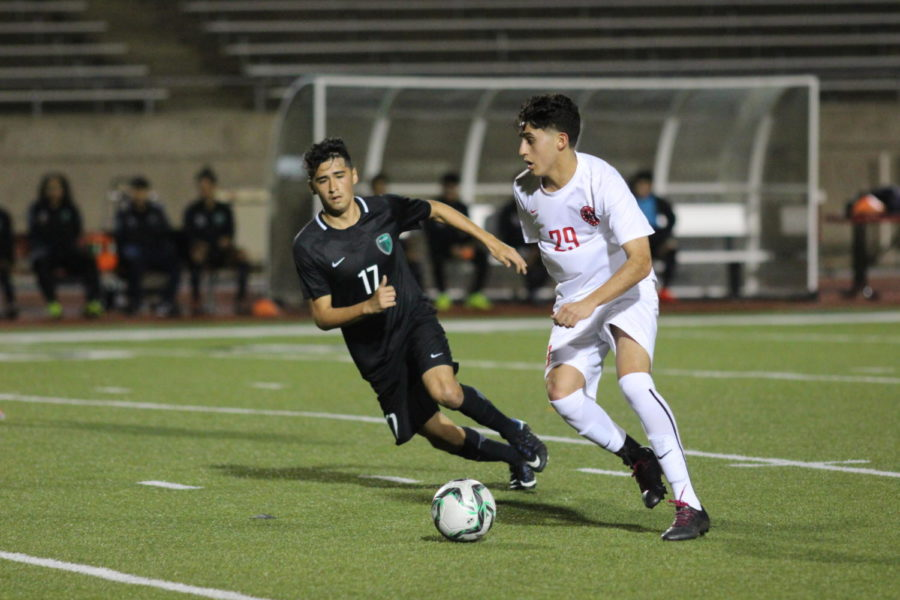 Coppell Cowboys senior midfielder Andrew Santillan looks to make a pass as Berkner Rams senior David Adame tries to steal the ball during the first half of the game on March 9 at Buddy Echols Field. The Coppell Cowboys defeated the Berkner Rams 5-1.