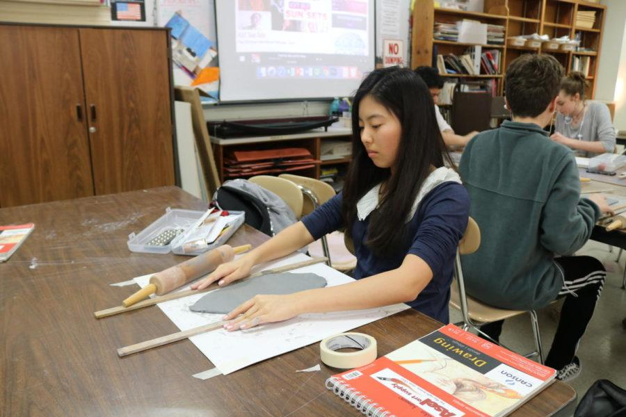 Freshman Haruka Kawano works on aligning her wooden tools to create the perfect slab. Wednesday at Coppell High School, students in David Bearden's Art I class create slabs on their first day of their new unit about ceramics.