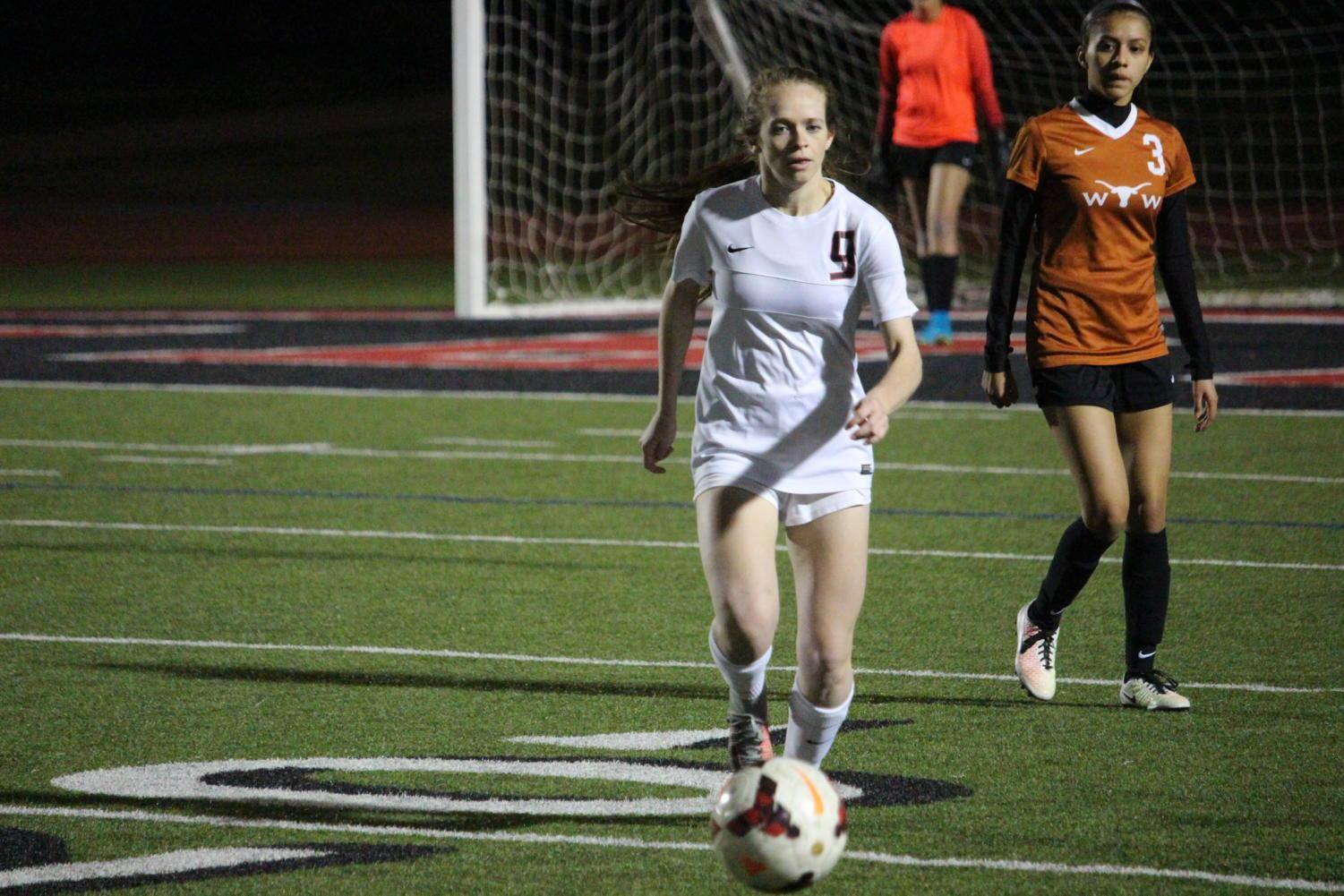 Coppell+High+School+senior+Rebecca+Watley+runs+for+the+ball+during+the+first+half+of+Tuesday+nights+home+game+at+Buddy+Echols+Field.+The+varsity+girls+soccer+team+played+against+WT+White+taking+the+win+with+a+score+of+5-1.
