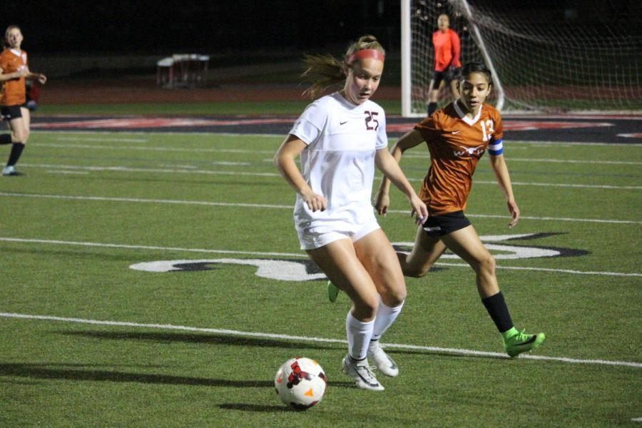 Coppell High School junior Mic Weathers defends the ball during the first half of Tuesday nights home game at Buddy Echols Field. The varsity girls soccer team played against WT White taking the win with a score of 5-1.