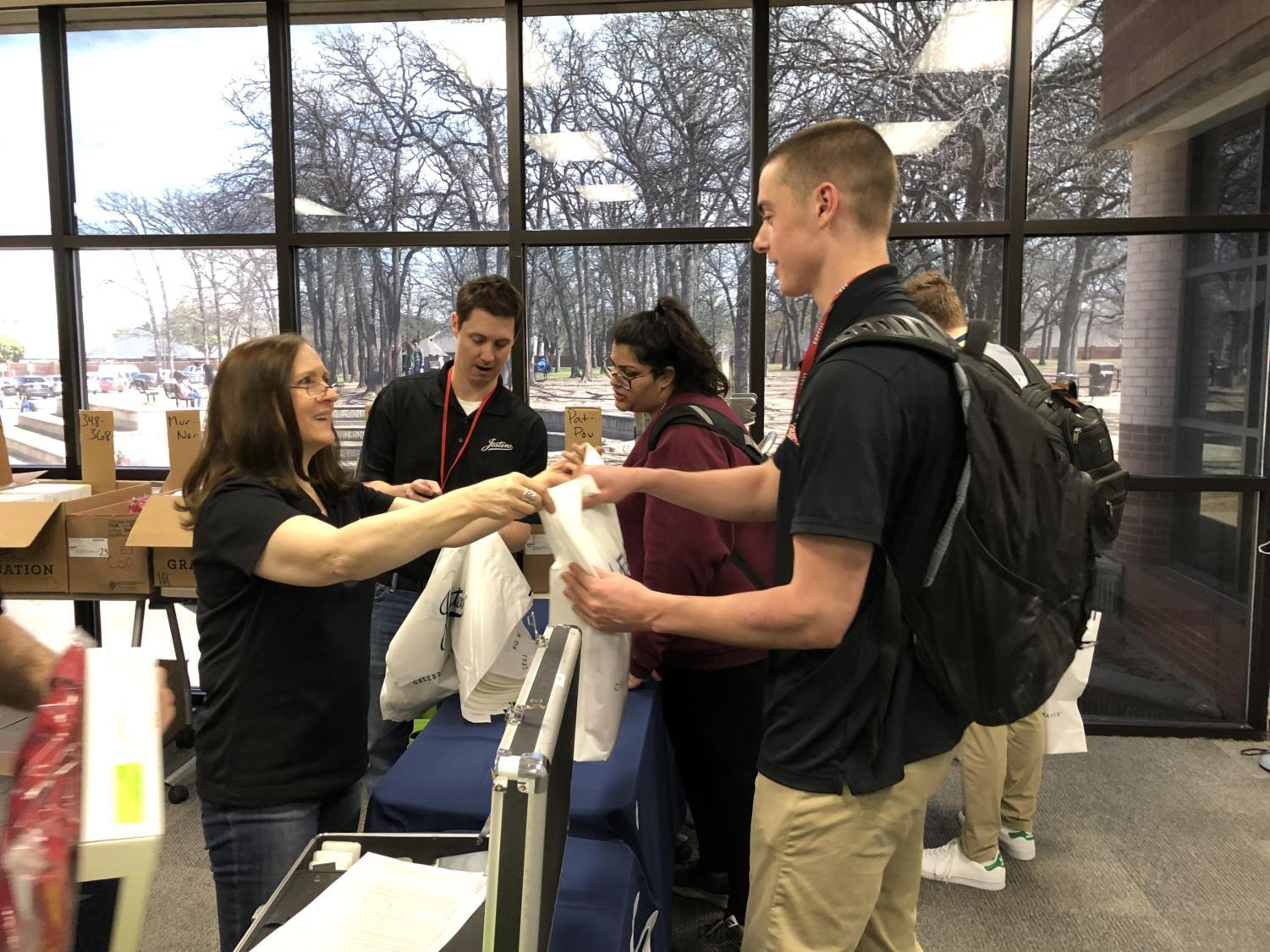 Coppell High School senior Hayden Lawrence picks up his cap and gown in the library classroom. Jostens will be at the high school until 5 p.m. so that seniors can pick up their graduation orders.