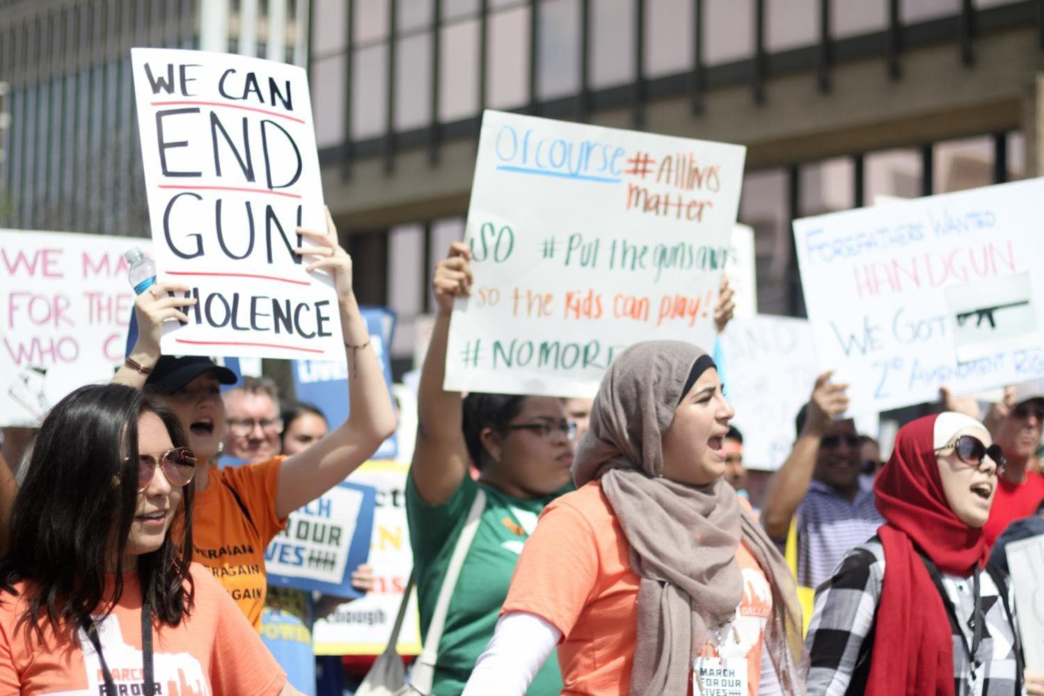 Marching protesters lift their signs and lead chants in support of gun control. On Saturday, protesters gathered to speak out against gun violence in the March For Our Lives in Dallas.
