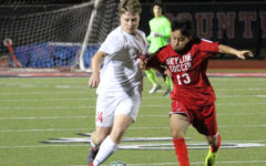 Coppell High School senior defender Thomas Grimmer runs with the ball alongside Skyline junior midfielder Edgar Munoz during the first half of the game on senior night March. 20. The Cowboys won the game against the Raiders 6-0.