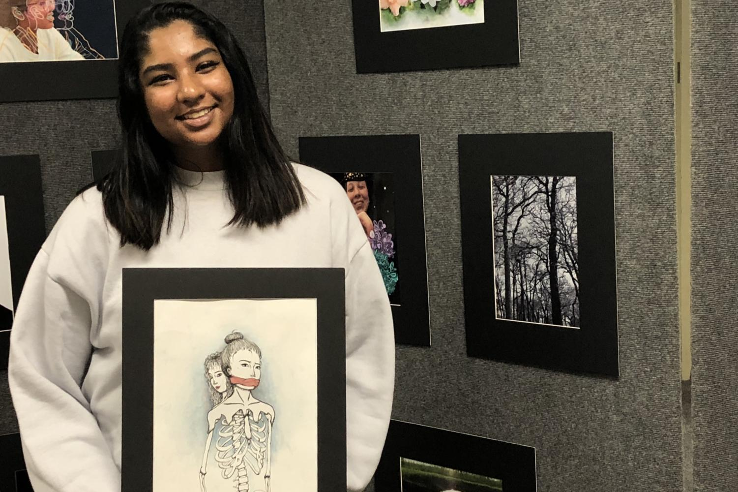 "Coppell High School sophomore Anjali Satpathy stands with her original artwork, entitled ""To the Bone"", which she entered in the Visual Arts Scholastic Event (VASE) competition on Feb. 24. Satpathy is also one of several CHS students volunteering at the Junior VASE event on Saturday at Coppell Middle School North."