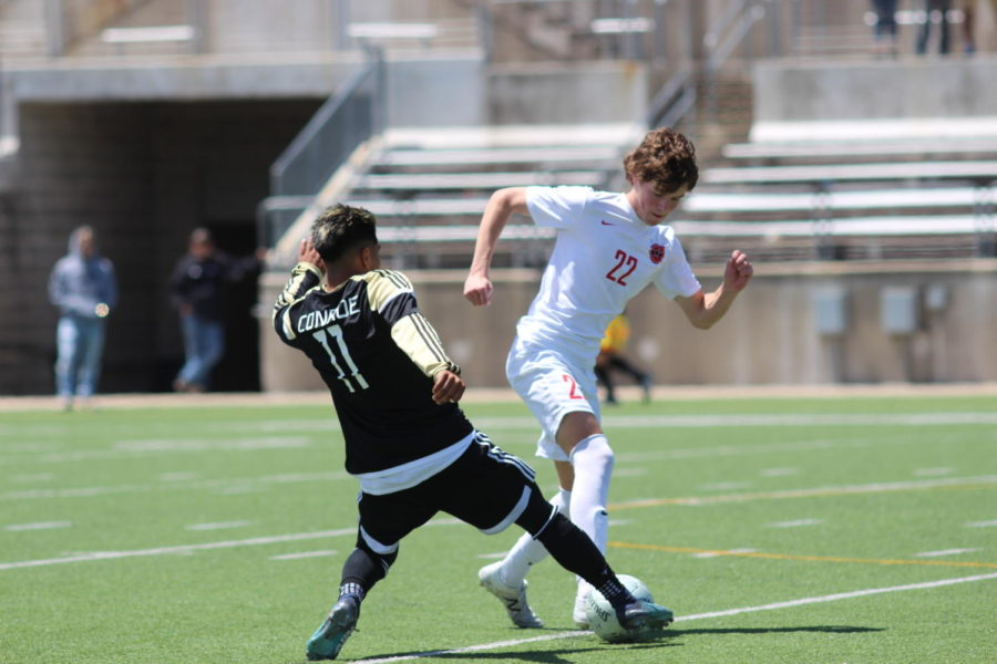 Coppell+Cowboys+sophomore+midfielder+Maxwell+Winneker+looks+to+make+a+pass+as+Conroe+Tigers+junior+midfielder+tries+to+steal+the+ball+during+the+first+half+of+the+Region+II+6A+Soccer+Tournament+on+April+14+at+Kelly+Reeves+Athletic+Complex+in+Round+Rock.+The+Cowboys+advanced+to+state+after+defeating+the+Tigers+1-+0.+Photo+by+Karis+Thomas