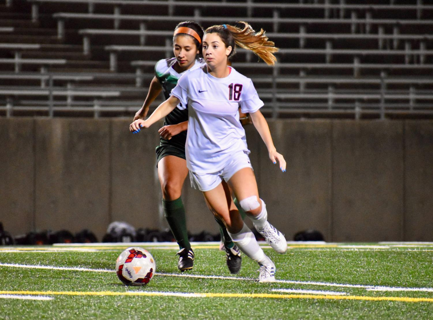While keeping the opposing team from scoring, Coppell High School sophomore defender Montserrat Lomeli looks for an open pass during the game against the Naaman Lady Rangers on March 29 at the John Clark Field. The Coppell Cowgirls will play again On Friday at Kelly Reeves Athletic Complex in Round Rock.