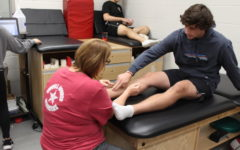 Coppell High School freshman track runner  Zach Stricker talks with Coach Yevtte Carson about his leg Monday morning in the athletic trainers room. Athletes are encouraged to talk to the trainers about any issues regarding their physical health.