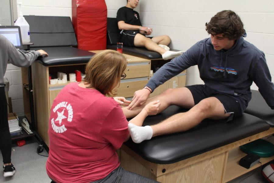 Coppell+High+School+freshman+track+runner++Zach+Stricker+talks+with+Coach+Yevtte+Carson+about+his+leg+Monday+morning+in+the+athletic+trainers+room.+Athletes+are+encouraged+to+talk+to+the+trainers+about+any+issues+regarding+their+physical+health.