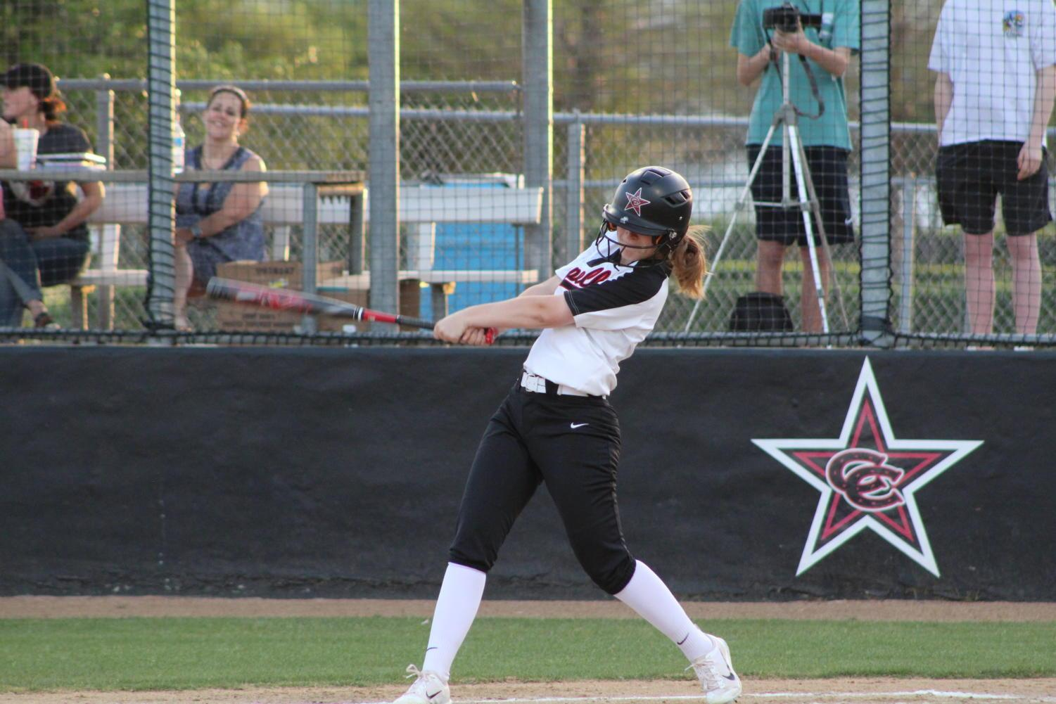 Coppell High School senior and left fielder Claire George hits the ball across the field at the CISD Baseball/Softball Complex  on Tuesday night. The Cowgirls varsity softball team won Tuesday night's home conference game against the Berkner Lady Rams with  a score of 2-1.