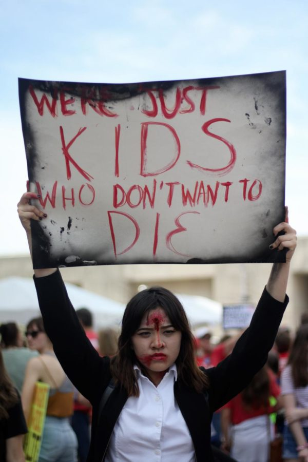 Mansfield Timberview High School junior Jac Nguyen raises her poster at March for Our Lives in downtown Dallas on March 24. The march was attended by approximately 7,000 demonstrators in support of gun control and school safety.