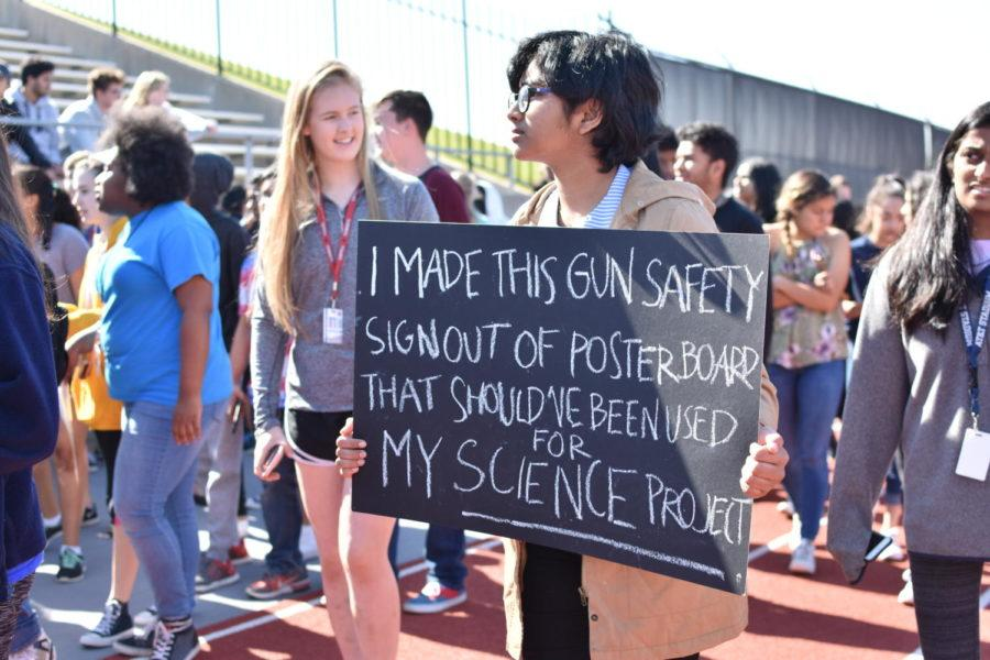 Coppell High School freshman Kirthika Piratla walks out with her poster at the Coppell High School walkout today in the track. The walkout was attended by approximately 700 high school students in support of gun control and school safety.