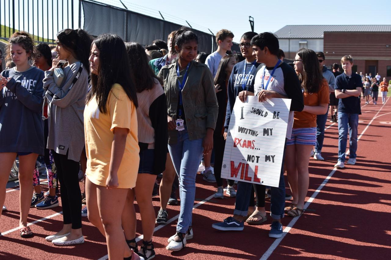 Coppell+High+School+students+walk+out+with+posters+at+the+Coppell+High+School+walkout+today+in+the+track.+The+walkout+was+attended+by+approximately+700+high+school+students+in+support+of+gun+control+and+school+safety.%0A