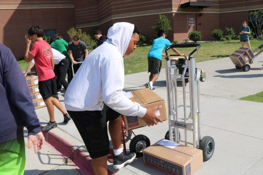 After school today, Round-Up staff members and Coppell Cowboys football players unloaded the yearbook trucks and divided the arena into alphabetized sections. Yearbooks will be distributed tomorrow in the arena from 7:45 a.m. to 3 p.m. for those who pre-purchased.