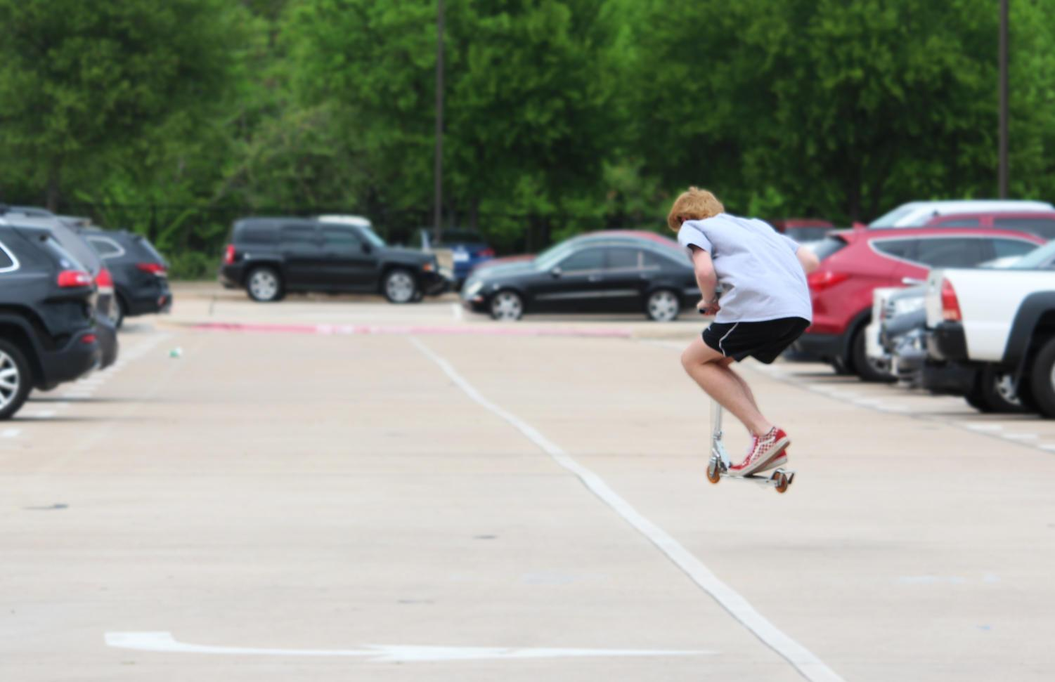 A student does a jump on his scooter in the student parking lot as students are released after fourth period for eighth period release. In the student parking lot students can be seen walking to or from their cars listening to music, talking to their friends and looking at their phones all while dodging traffic.