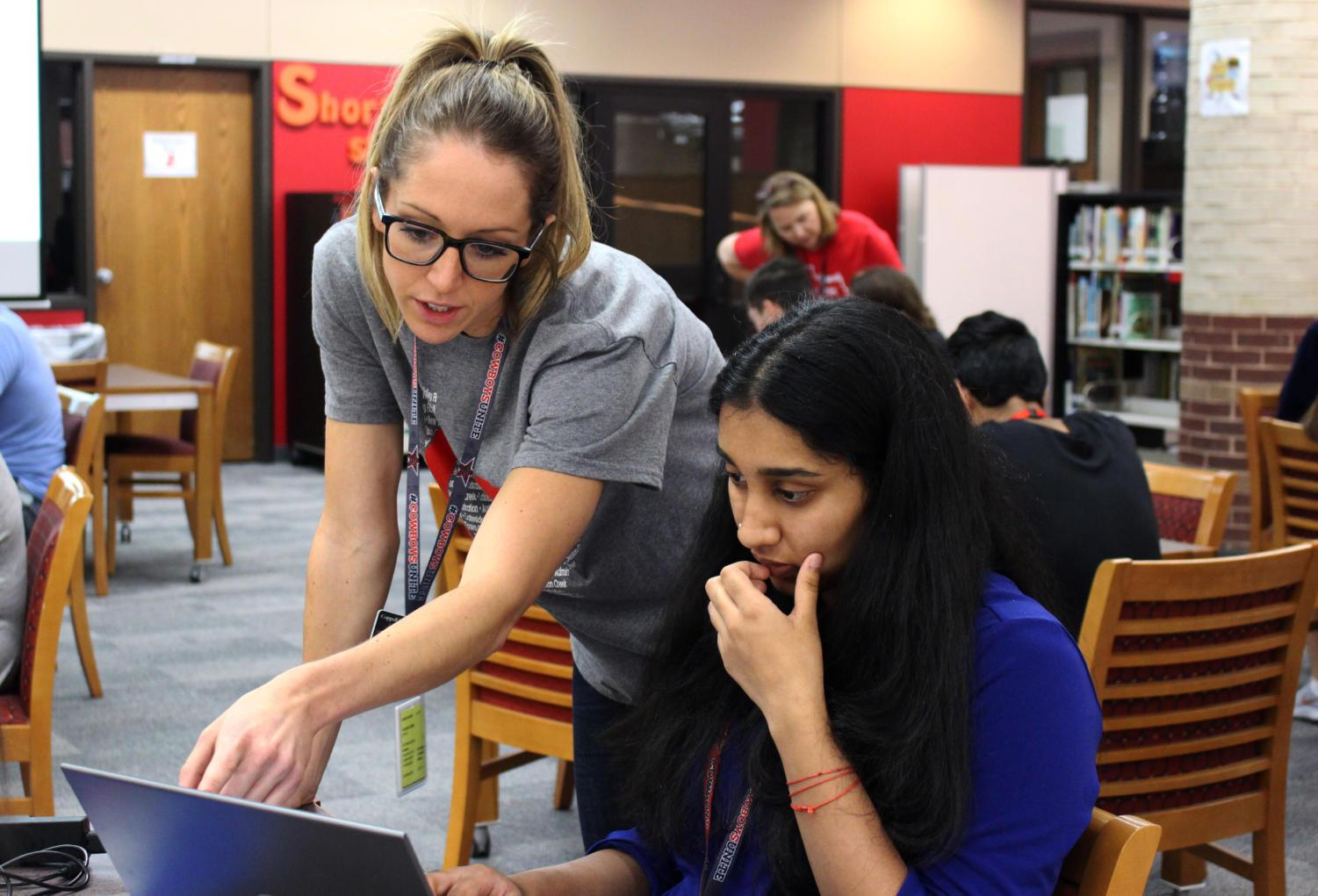 During 6th period, Coppell High School English III teacher M'Lynn Creighton helps a student find a book for Sustained Silent Reading (SSR) using the browser, Destiny, in the library. Creighton is a new teacher who recently moved from Pismo Beach, Calif.