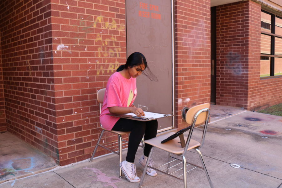 Coppell High School junior Varsha Chintapenta works on drawing images from her phone in Michelle Hauske's AP Drawing class. This class involves developing different skills such as drawing and creativity.