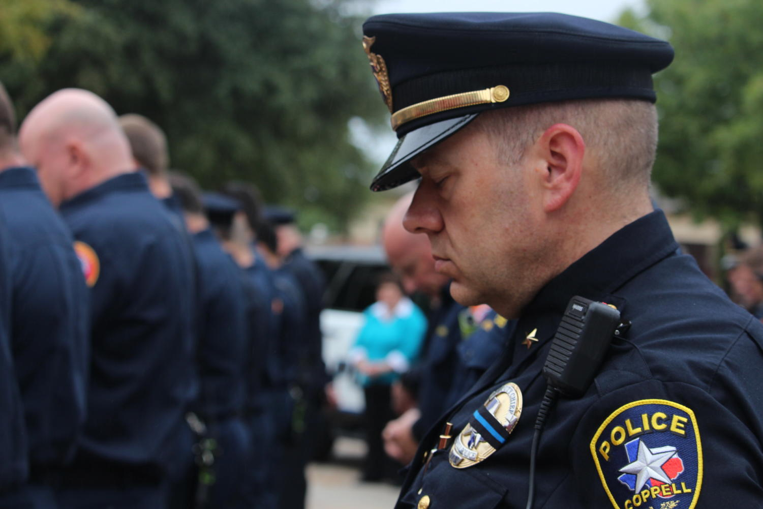 During the Patriot Day ceremony on the morning of Sept. 11, Coppell Deputy Chief Jim Cook bows his head in prayer with his fellow officers before Coppell Town Center Hall. In honor of the lives of those lost 17 years ago, a moment of silence is taken by the attendees to commemorate the loss of the victims and the bravery shown in the last moments of their lives during the 9/11 terrorist attacks.