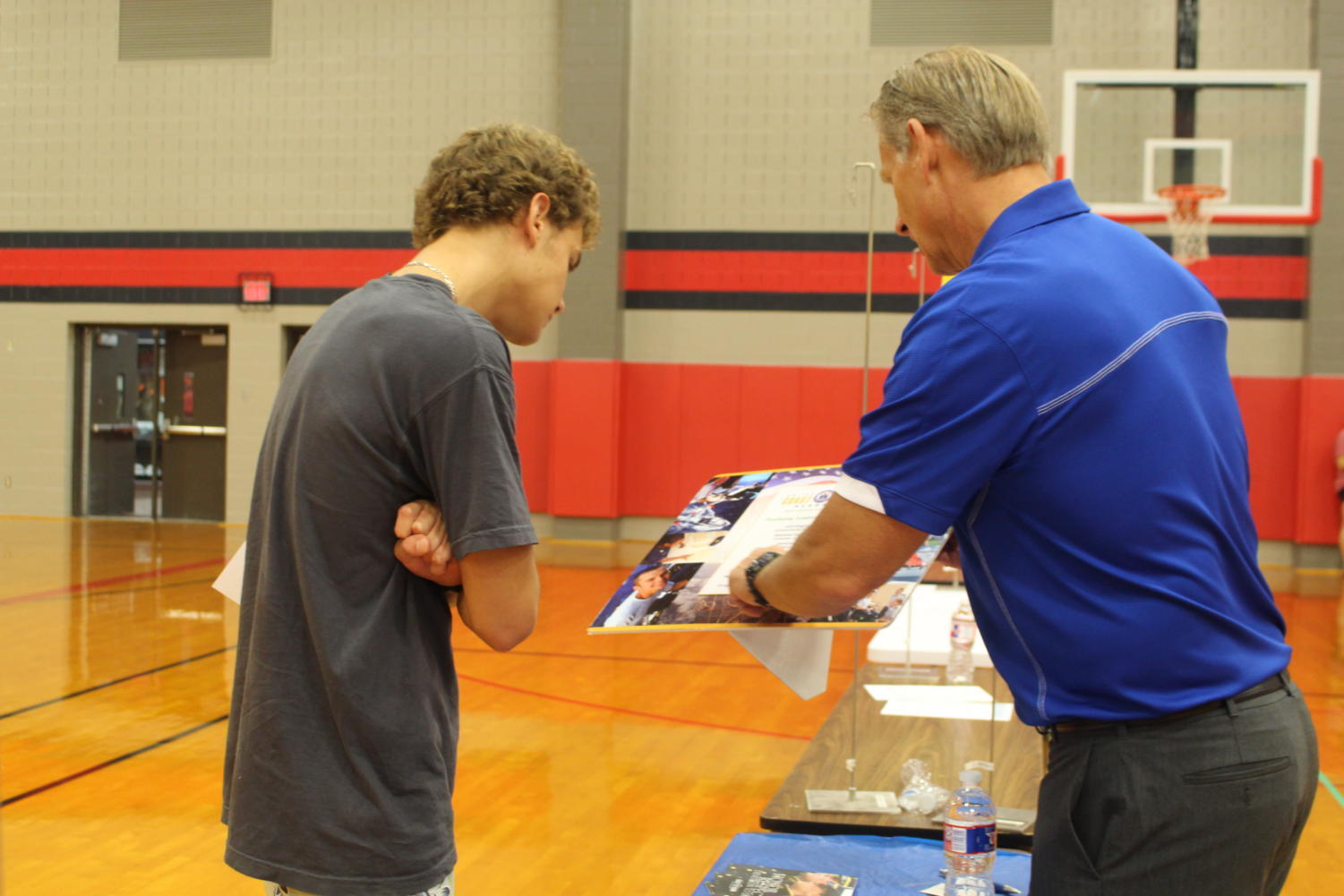 Coppell High School junior Johan Pretorius listens to Jason Oswald from the United States Coast Guard about the requirements and opportunities he can earn from this program. Oswald uses a pamphlet to explain these details.