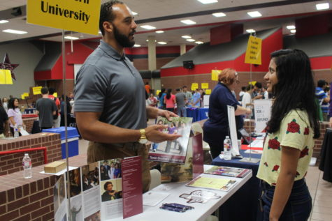 Derrick McKee from Texas Southern University explains to Coppell High School junior Anusha Karekar talks about the basics of the University such as the requirements and degrees they offer.