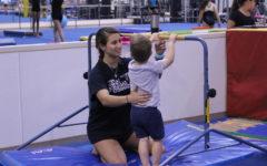 Coppell High School senior Sophia Olson coaches one of her 2 year old students to do a backflip on a bar during Gymnastics practice. Olson helps by supporting the students back to help guide him to flip over.