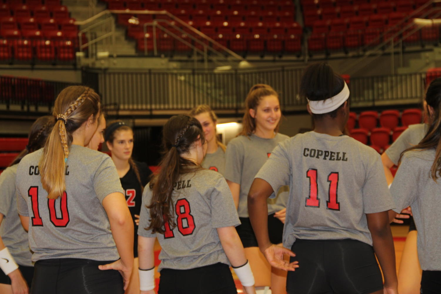 The varsity volleyball team circles up before their match against the Irving Nimitz this past Friday night in the arena.