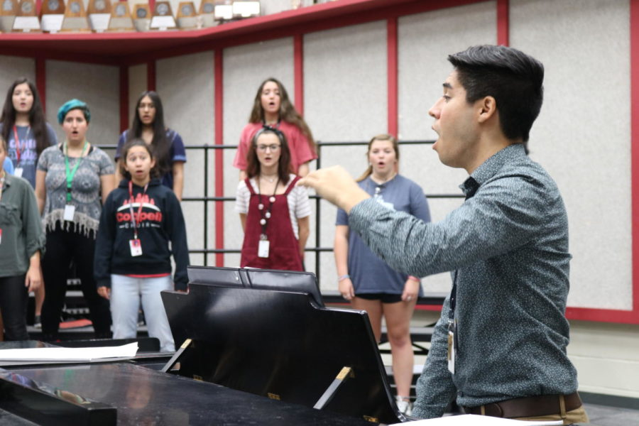 Coppell High School choir director Aaron Coronado help students of Kantorei, the women's varsity treble choir, warm up through vocal exercises during Bona Coogle and Coronado's third period choir class. The choir department has been preparing for their upcoming fall concert on October 2nd.