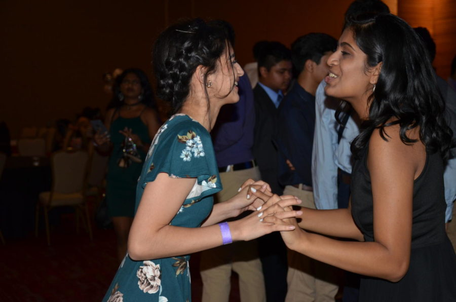 Coppell juniors Amsah Rauf and Mansi Patel sing and dance together at Coppell High School's annual homecoming dance on Saturday night at Irving Convention Center. In the week leading up to the dance, there are numerous traditions in CHS, including spirit week and mums and garters.