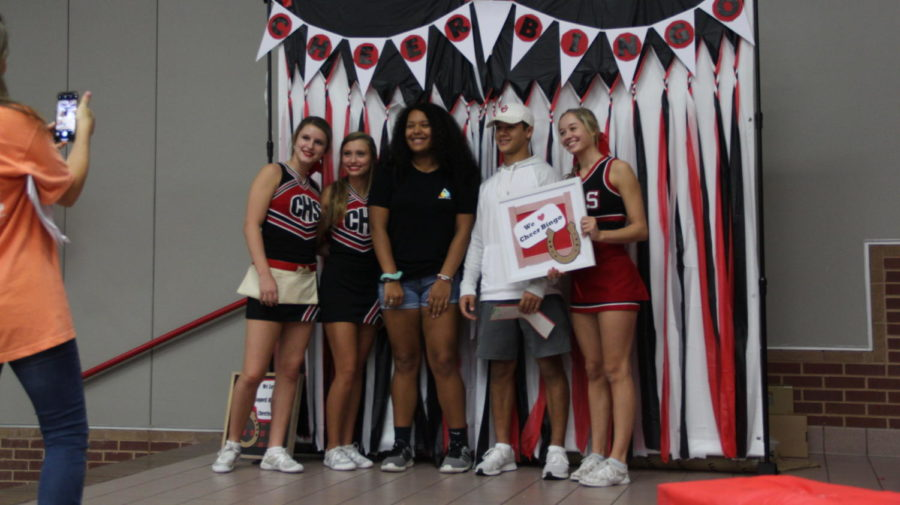 Junior varsities sophomore cheerleaders Katy Kryzak, Taylor Kniff and senior varsity cheerleader Laurie Sanford takes a picture with the winning bingo players on Friday Sept. 23 at Coppell High School. Once you yell bingo and match all the spots you can win a prizes such as gift cards, money, and more.