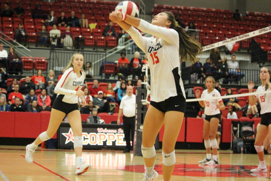 Coppell senior setter Stella Yan prepares to hit the ball over the net to score a point on Oct.19 at the CHS Arena. The Cowgirls defeated Flower Mound Marcus 3-1. Photo by Neveah Jones.
