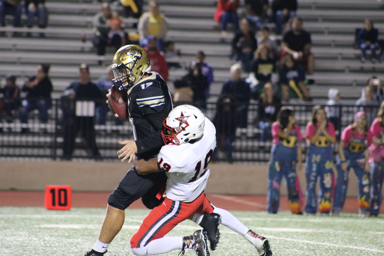 Coppell High School senior Xavier Brown tackles Irving quarterback, junior Josh Buckett, during the game at Joy & Ralph Stadium on Oct. 26. The Cowboys beat the Tigers, 48-13.