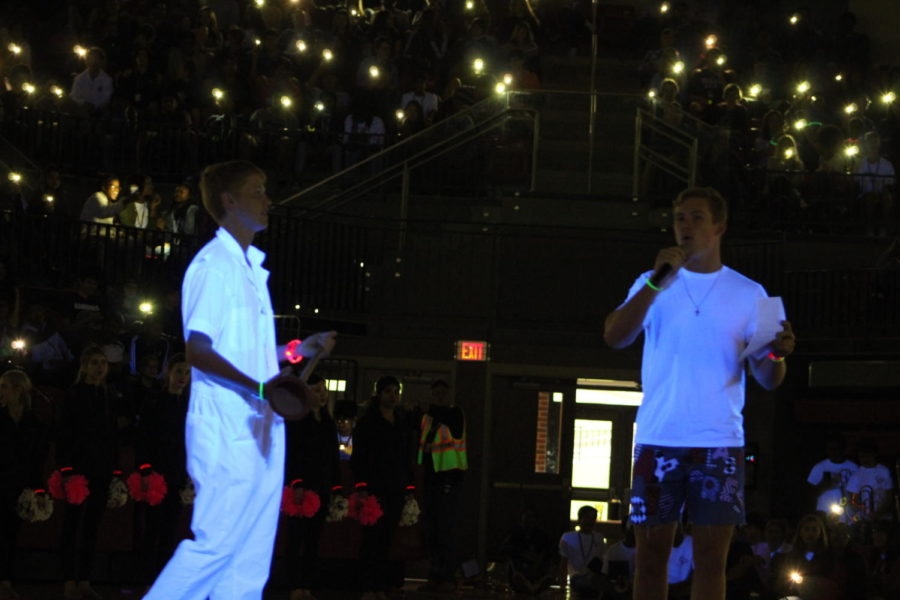 """Coppell High School senior President Jay Dempsey, and senior """"plunger boy"""" Nathan Payan lead the pep rally in the CHS Arena on Oct. 19. CHS blackout pep rally is when students wear neon and white, while the light are out, and the cheerleaders, larriettes, and band perform."""