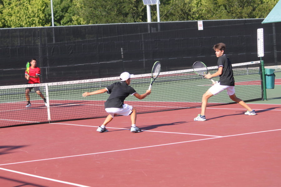 Coppell High School varsity tennis player junior Mihiro Suzuki and freshman Andreja Zrnic dive to hit the ball during their second set against Marcus High School on September 18. Suzuki moved to Coppell from Japan before his sophomore year of high school and has found a home on the tennis team.