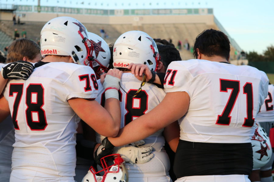 Coppell players share a hug with assistant coach Blake Johnson after the playoff game at Dragon Stadium on Nov. 17. The Carroll Dragons ended the game, 54-10, over Coppell, ending the Cowboys' season.