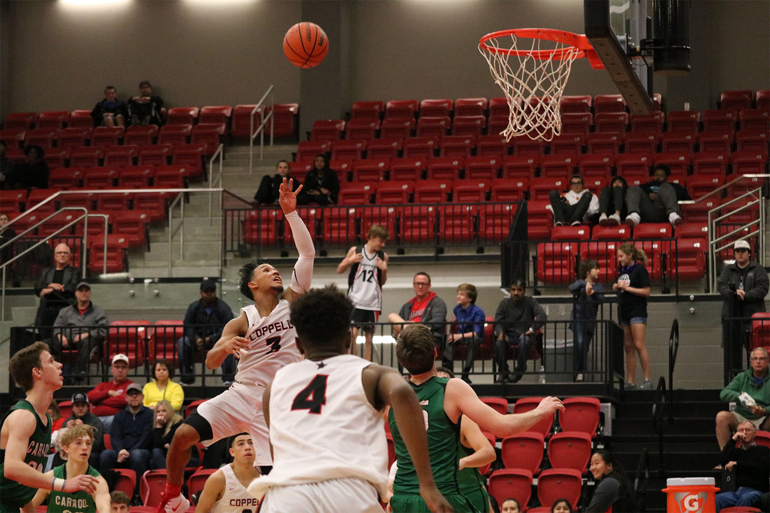 Coppell senior guard Tariq Aman goes up for a layup on Saturday against Carroll in the CHS arena. The Cowboys lost to the Dragons, 70-53, in their first game of the season.