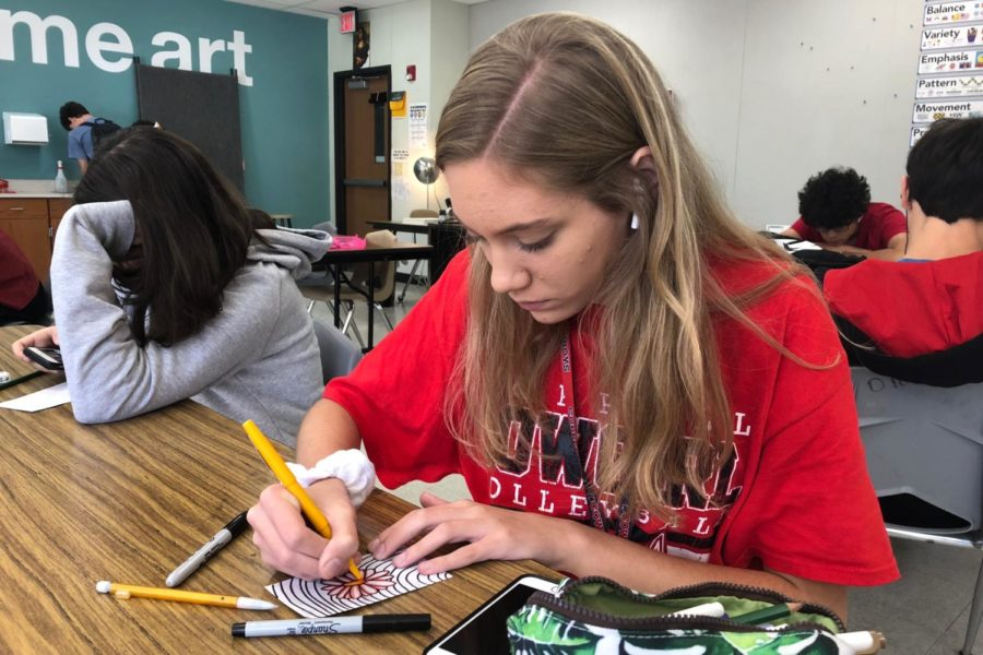 Coppell+High+School+sophomore+Christiana+Reimer+illustrates+a+flower+on+a+notecard+in+David+Bearden%E2%80%99s+second+period+Art+I+class+on+Oct.+29+for+the+geocache+art+experiment.+In+the+project%2C+students+hide+their+artworks+around+the+school+and+leave+hints+for+other+students+to+find+them.+