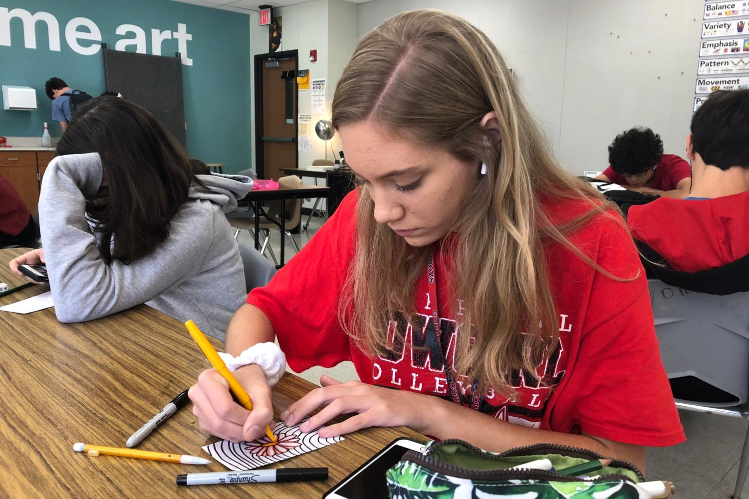Coppell High School sophomore Christiana Reimer illustrates a flower on a notecard in David Bearden's second period Art I class on Oct. 29 for the geocache art experiment. In the project, students hide their artworks around the school and leave hints for other students to find them.
