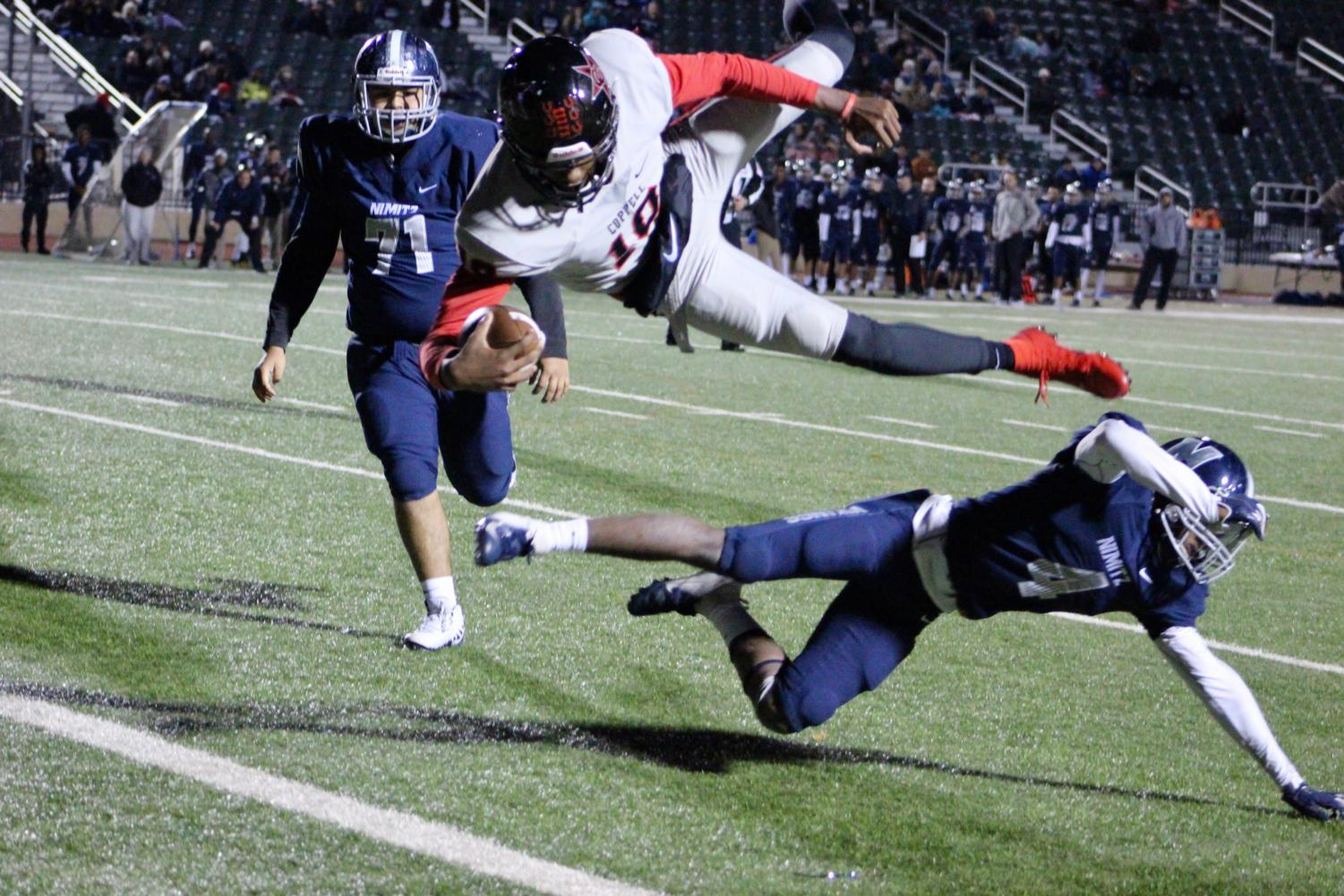 Coppell senior quarterback Taj Gregory dives into the end zone for a touchdown against Irving Nimitz on Nov. 9 at Joy and Ralph Ellis Stadium. The Cowboys defeated the Vikings, 35-14.