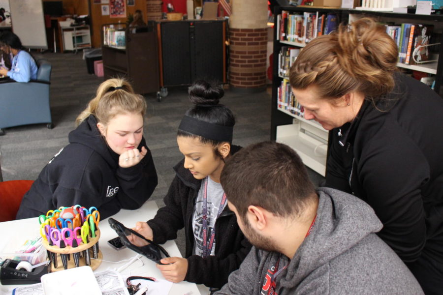 """During fifth period, Coppell High School English IV and Girls basketball coach Kristen Davis helps CHS seniors Kendyll Keyes, Anya D'Silva, Michael Widish discuss a strategy for digital game English IV Asylum LA activity on Wednesday, Dec. 13th. The English IV teachers have worked on a new way for students to learn about the well known books, """"Hamlet, Othello, and Macbeth"""" is the main focus of the activity."""