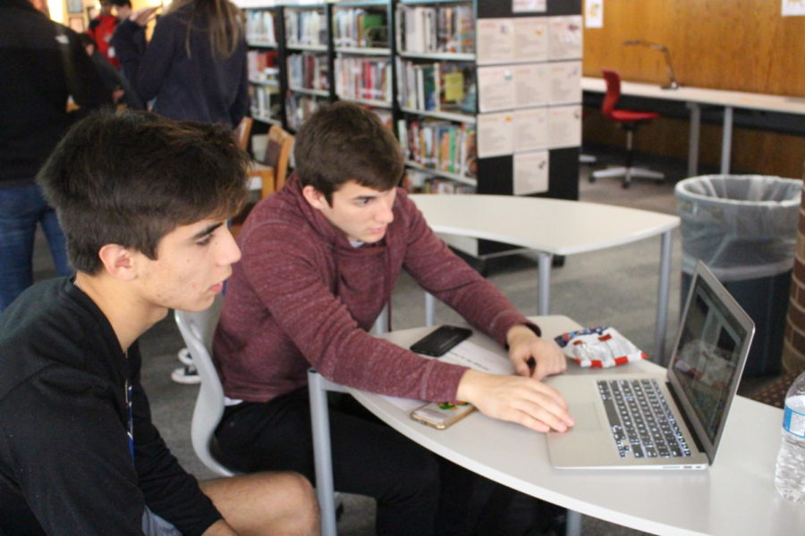 """During fifth period, Coppell High School seniors Jacob Vasquez, Jake Stricter  discuss a strategy for digital game English IV Asylum LA activity on Wednesday, Dec. 13th. The English IV teachers have worked on a new way for students to learn about tree well known books, """"Hamlet, Othello, and Macbeth"""" is the main focus of the activity."""