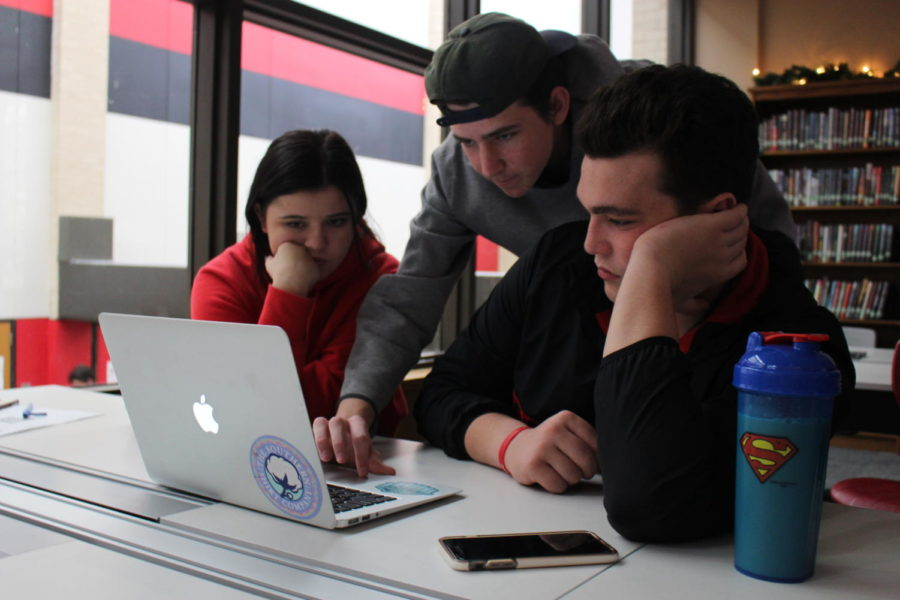 """During fifth period, Coppell High School seniors Annie Hassman, Teddy Solari, Jack Lookabaugh discuss and strategy for digital game English IV Asylum LA activity on Wednesday, Dec. 13th. The English IV teachers have worked on a new way for students to learn about tree well known books, """"Hamlet, Othello, and Macbeth"""" is the main focus of the activity."""