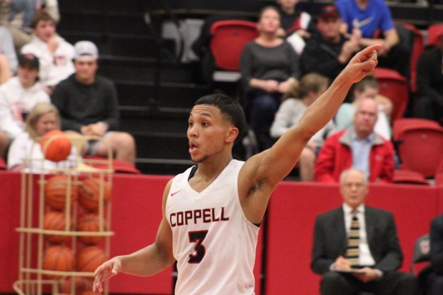 Coppell High School senior guard Tariq Aman directs his teammates while waiting for a pass. The Cowboys defeated Rockwall Heath, 59-55, on Tuesday in the CHS arena.