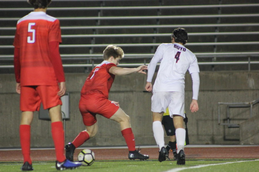 Coppell High School senior, Blake Bartlett guards the ball against McKinney Boyd during the game on Jan.15th against McKinney Boyd, at Buddy Echols Field. Cowboys lost the battle to the Broncos 3-2.