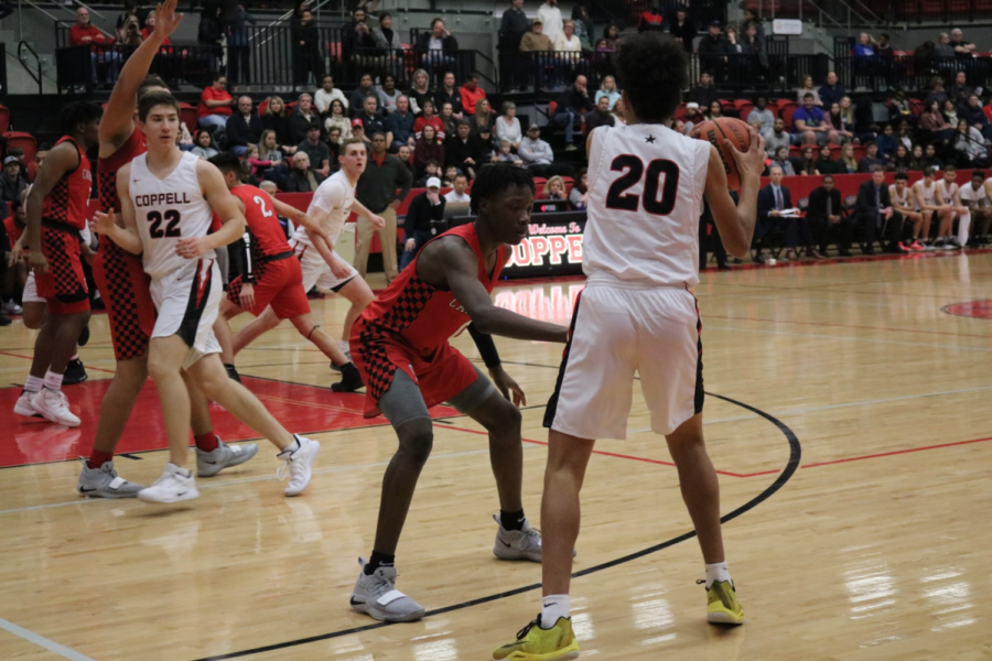 Coppell+High+School+freshman+Anthony+Black+protects+the+ball+from+the+Macarthur+Cardinals.+The+Coppell+varsity+basketball+team+won+56-55+against+the+Macarthur+Cardinals.